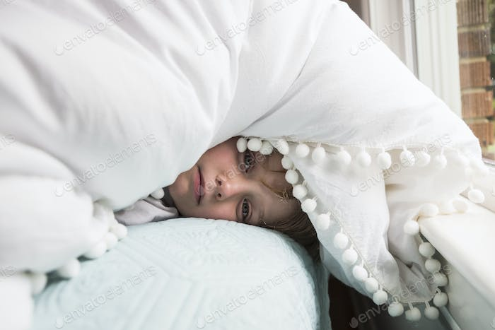 6 year old boy in bed with covers over his head