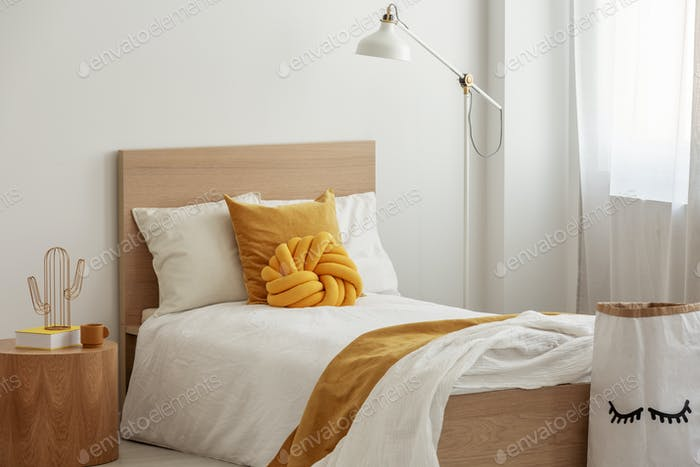 Tall industrial lamp over yellow pillows and blanket on white single wooden bed