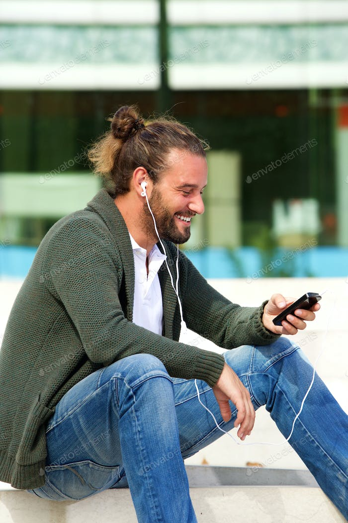 Smiling man sitting on steps listening to music with smart phone