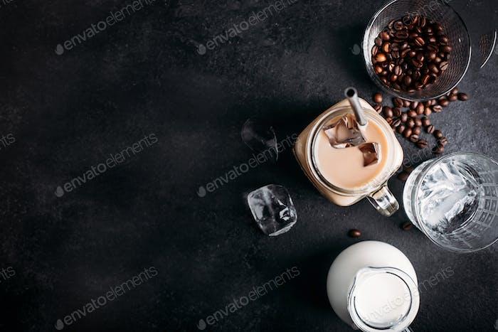 Kalter Eiskaffee mit Zutaten: Eiswürfel, Milch, Kaffeebohnen