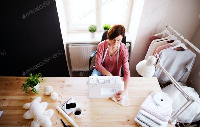 Young creative woman in a studio, working. A startup of tailoring business.