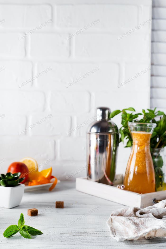 Orange lemonade in the decanter on a wooden tray and Cocktail shaker for preparing a summer cocktail