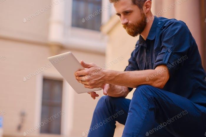 Бородатый самец сидит на ступеньке и с помощью планшета.