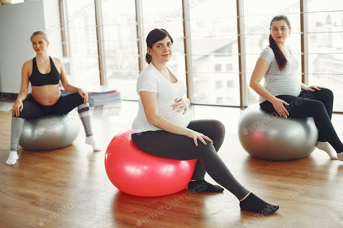 Pregnant women doing yoga in a gym