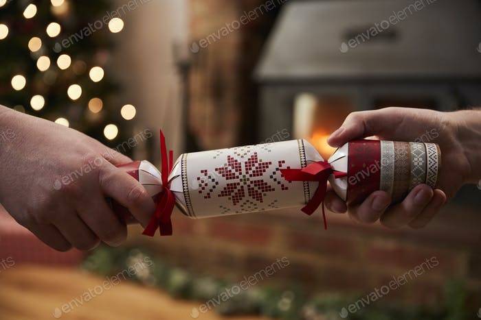 Couple Pulling Cracker In Room Decorated For Christmas