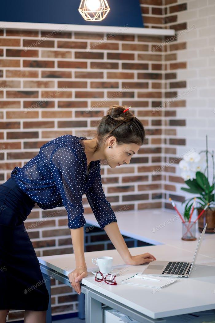 Geschäftsfrau im Büro auf der Suche nach dem Laptop