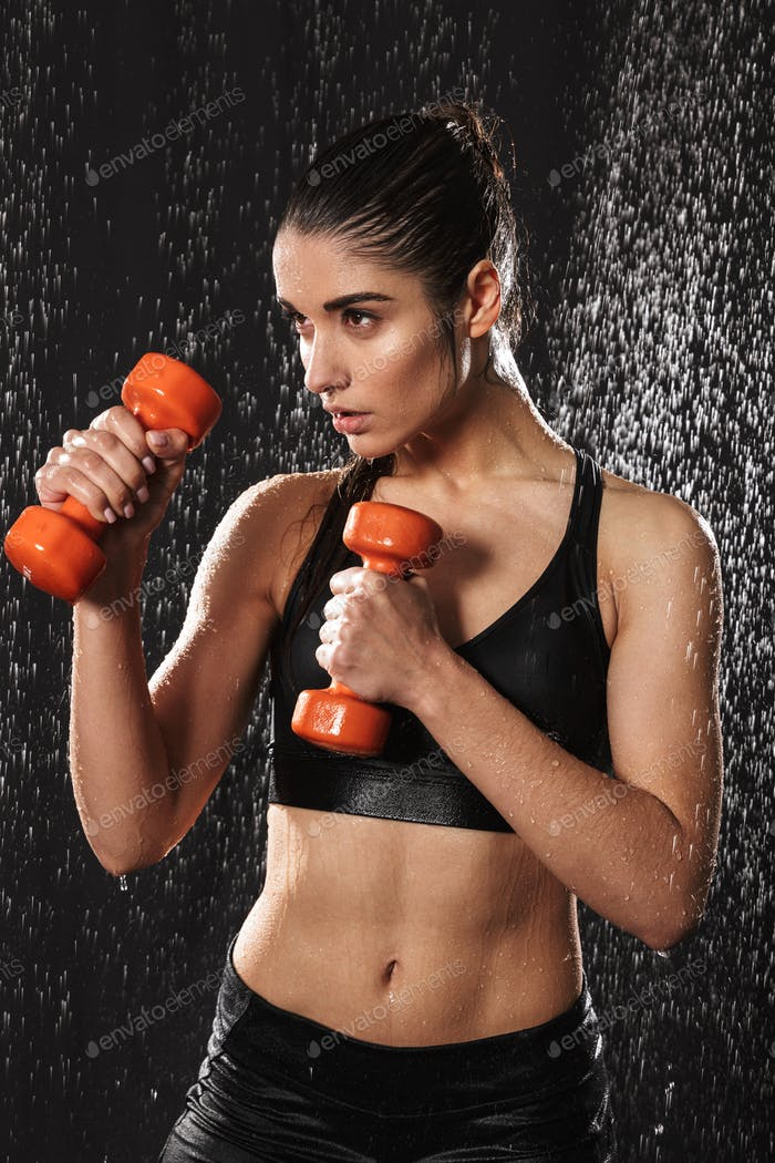 Portrait of a fit young sportswoman holding barbells