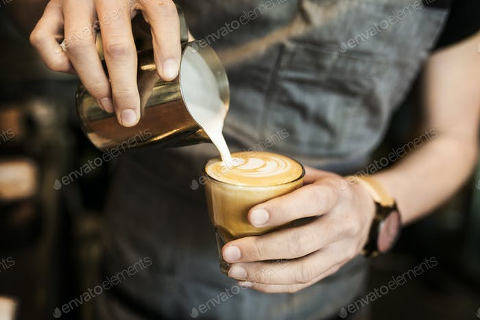 Mid section of barista preparing coffee