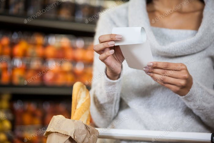 Mid section of woman holding bill