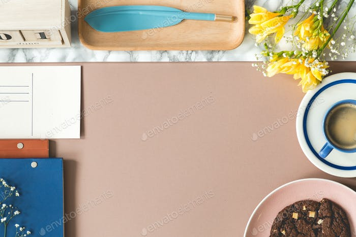 High angle of desk with flowers, coffee cup, notebooks and copy