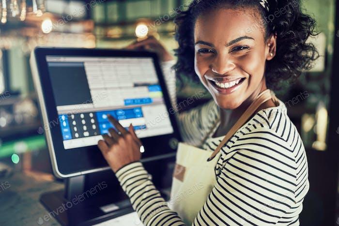 Lächelnd junge Kellnerin mit einem Restaurant Point of Sale Terminal