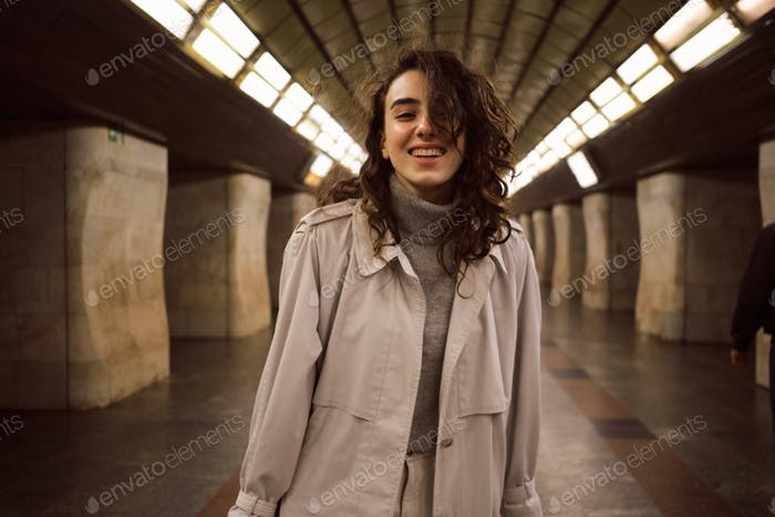 Portrait of cheerful casual girl in trench coat happily posing at subway station