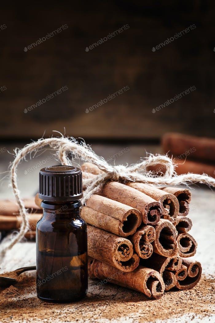 Essential cinnamon oil in a small bottle, ground cinnamon and cinnamon sticks