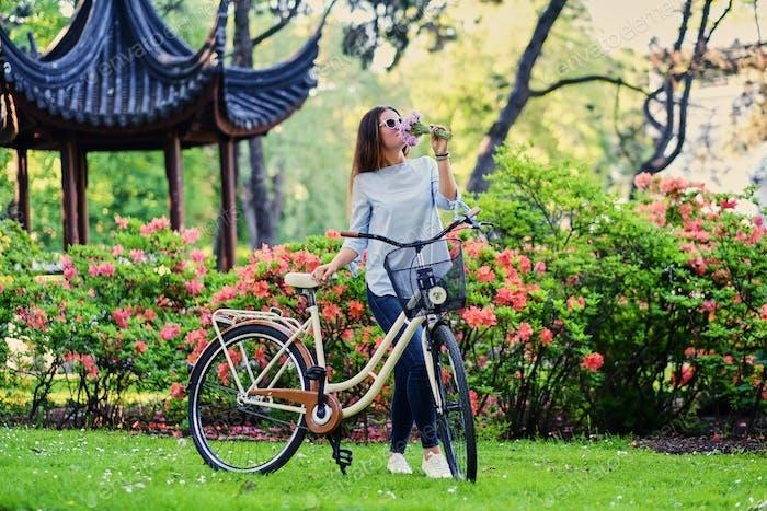 Eine Frau mit Stadtfahrrad in der Nähe des traditionellen chinesischen Pavillons in einem Park.