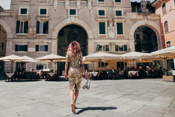 Back View of Elegant Glamorous Barefoot Girl in Golden Dress Walking in Verona, Italy