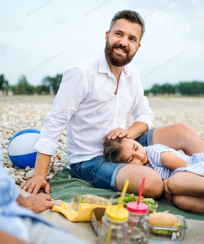 Father with tired daughter on a holiday by the lake, having picnic.