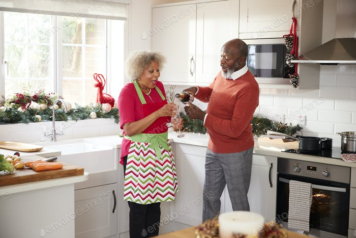 Senior black man pouring champagne for his partner on Christmas Day