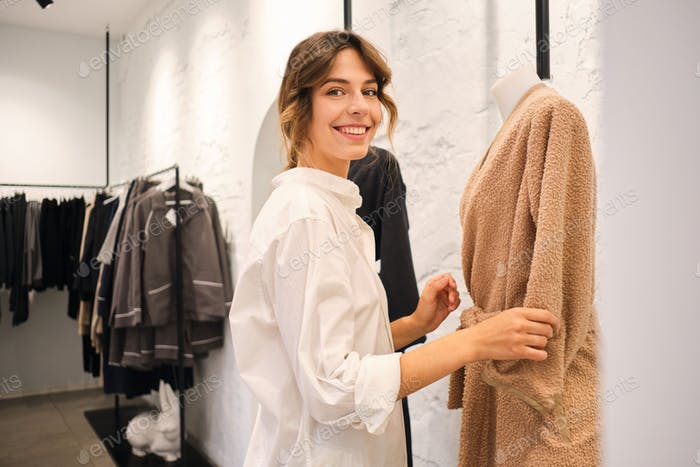 Smiling woman in workshop happily looking in camera making fitting of new collection on mannequin