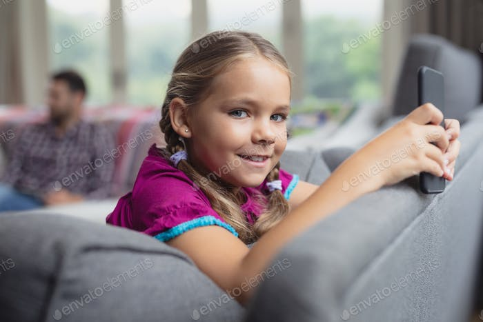 Cute Caucasian girl looking at camera while using mobile phone on sofa