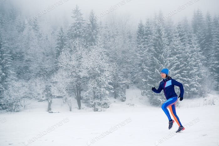 Trail running girl on snow in winter mountains