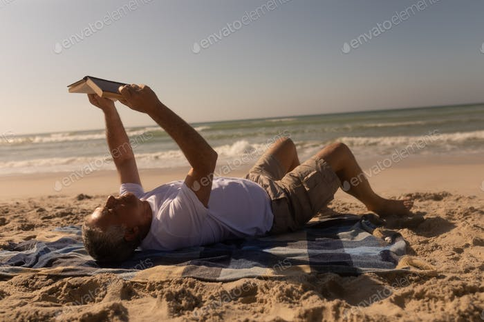 Side view of active senior man reading a book while relaxing on picnic blanket at beach