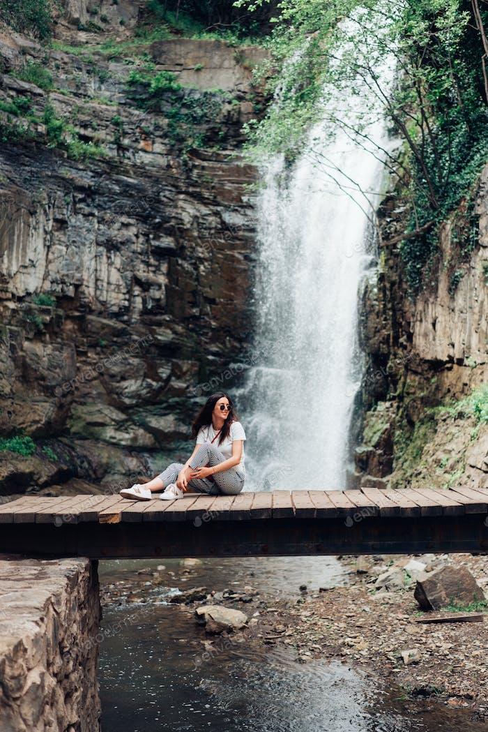 La chica se sienta en un Puente