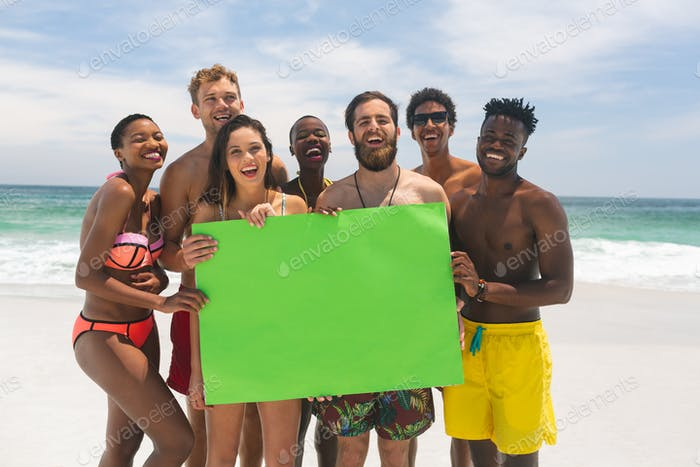 Happy group of diverse friends holding a empty green placard at beach on a sunny day.