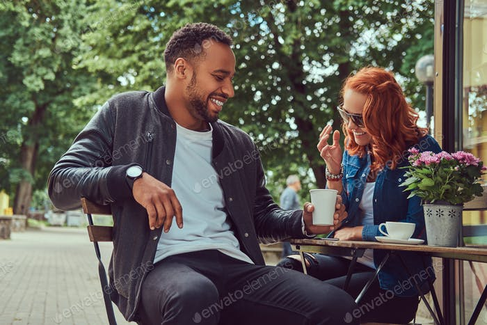 A couple dating drinking coffee, sitting near the coffee shop. Outdoors on a date.