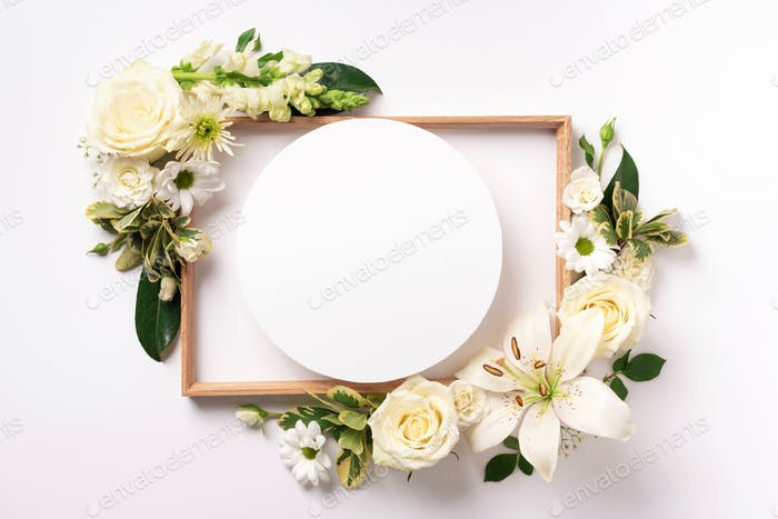 White roses, lily, gerbera and circle shape paper over light background. Flat lay, top view