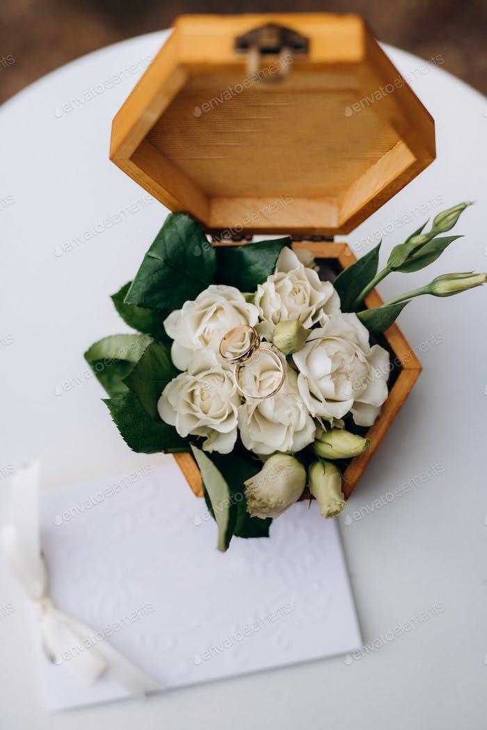 goldene Trauringe mit einem Hochzeitsdekor