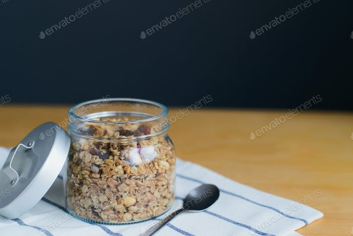 granola with peanuts, hazelnuts, oat and wheat flakes in glass jar