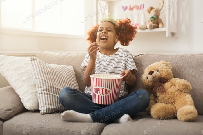 Laughing black little girl watching movie at home
