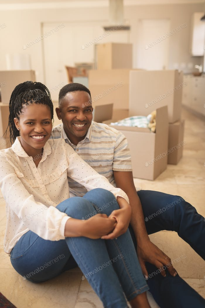Happy couple sitting on floor and looking at camera in a comfortable new home
