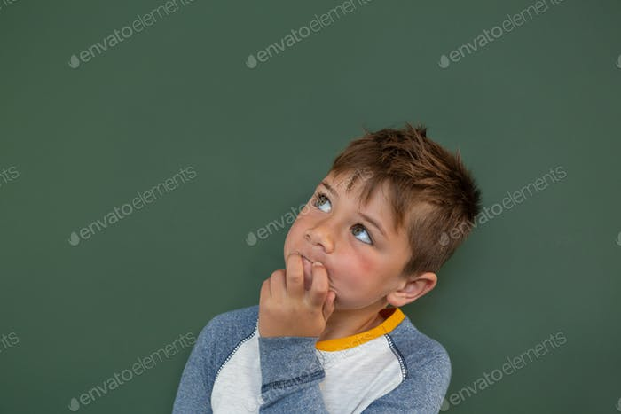 Thoughtful schoolboy standing against green chalkboard in a classroom at elementary school