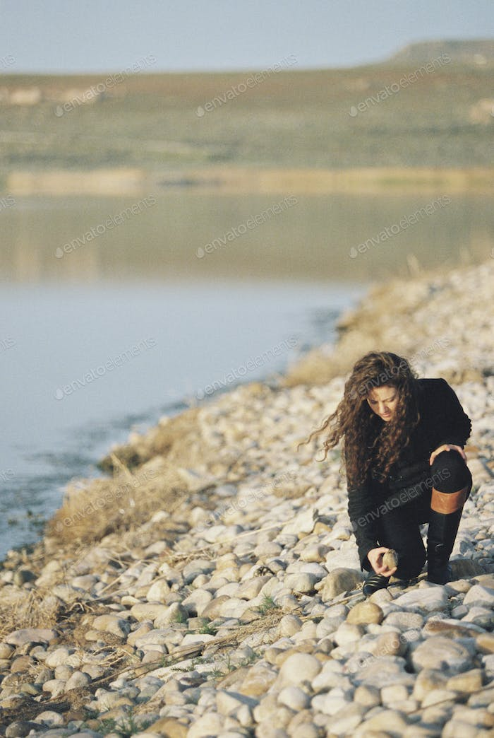 A woman collecting pebbles on the shore of a lake.