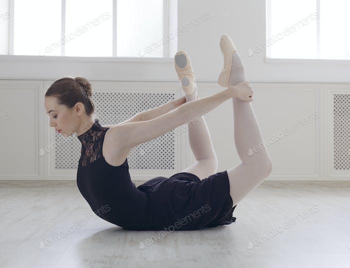 Beautiful ballerine practice bow pose, yoga stretching