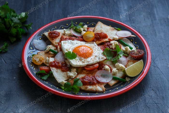 Chilaquiles Mexican tortilla with tomato salsa, chicken and egg close-up on a plate. Horizontal view