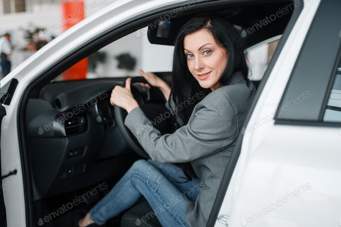 Woman buying new car in showroom
