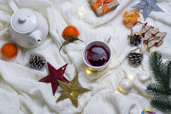 Cup of tea with tangerines and sweaters on bed background