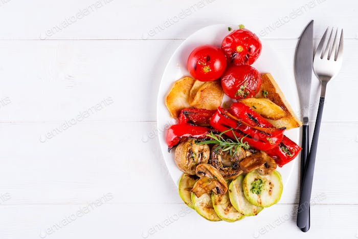 Grilled vegetables on a plate on white wooden background, flat lay