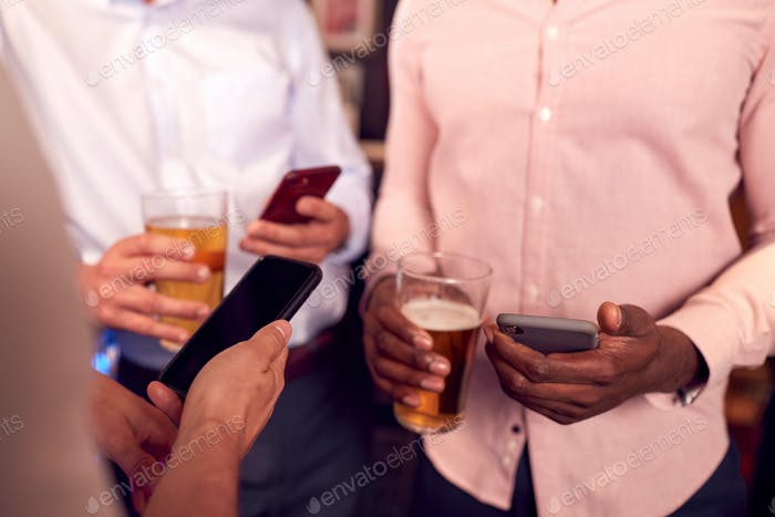 Group Of Male Friends All Checking Mobile Phones Whilst Meeting For Drink In Bar