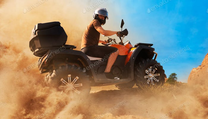 Atv in dust clouds, sand quarry on background