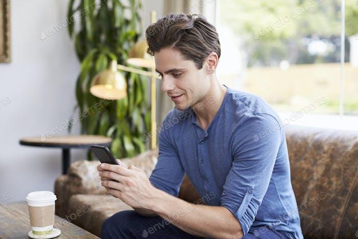Молодой кавказский мужчина пользуется смартфоном в кафе