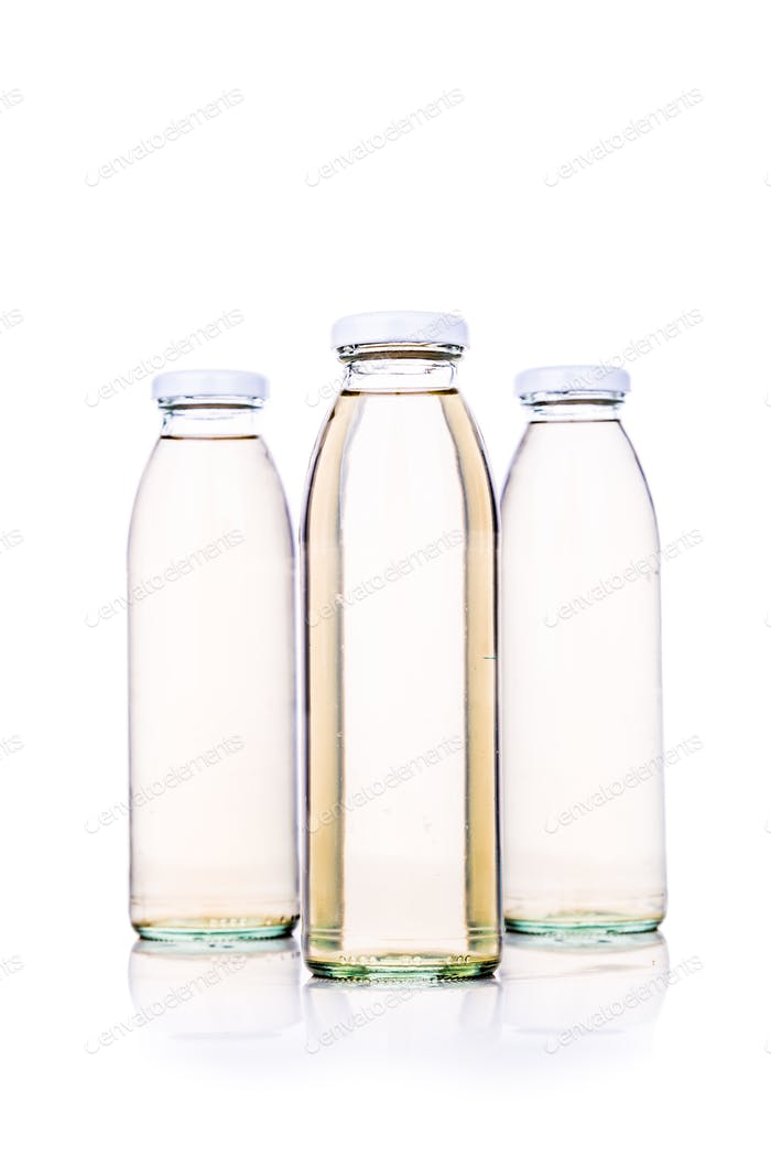 Translucent liquid in glass bottle on white background