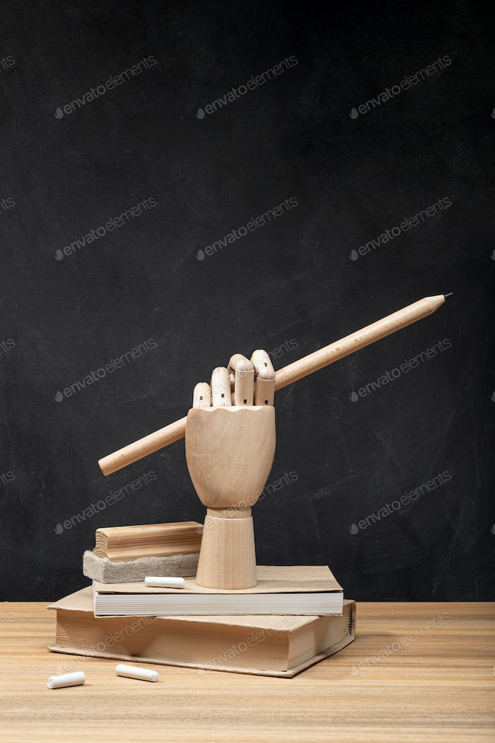Wooden hand holding a pencil on books