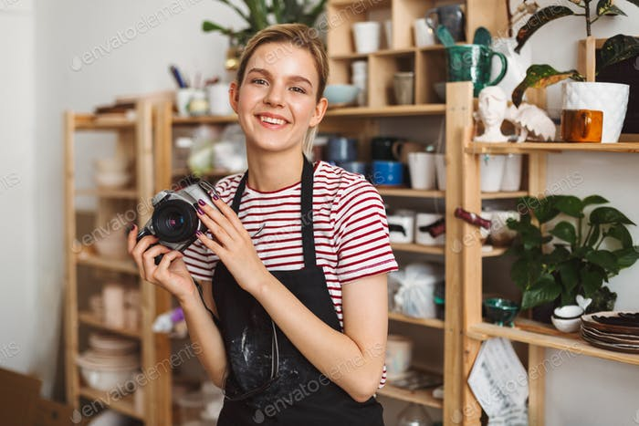 Smiling girl in black apron and striped T-shirt holding camera in hands happily looking in camera