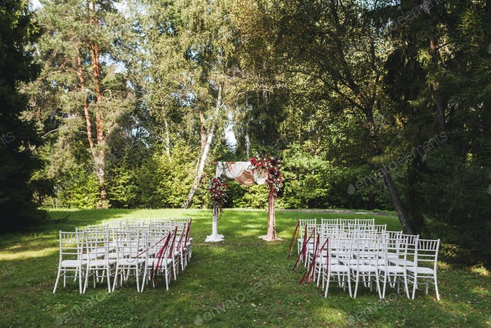 Wedding ceremony in rustic style decorated with different red flowers, white textile and chairs