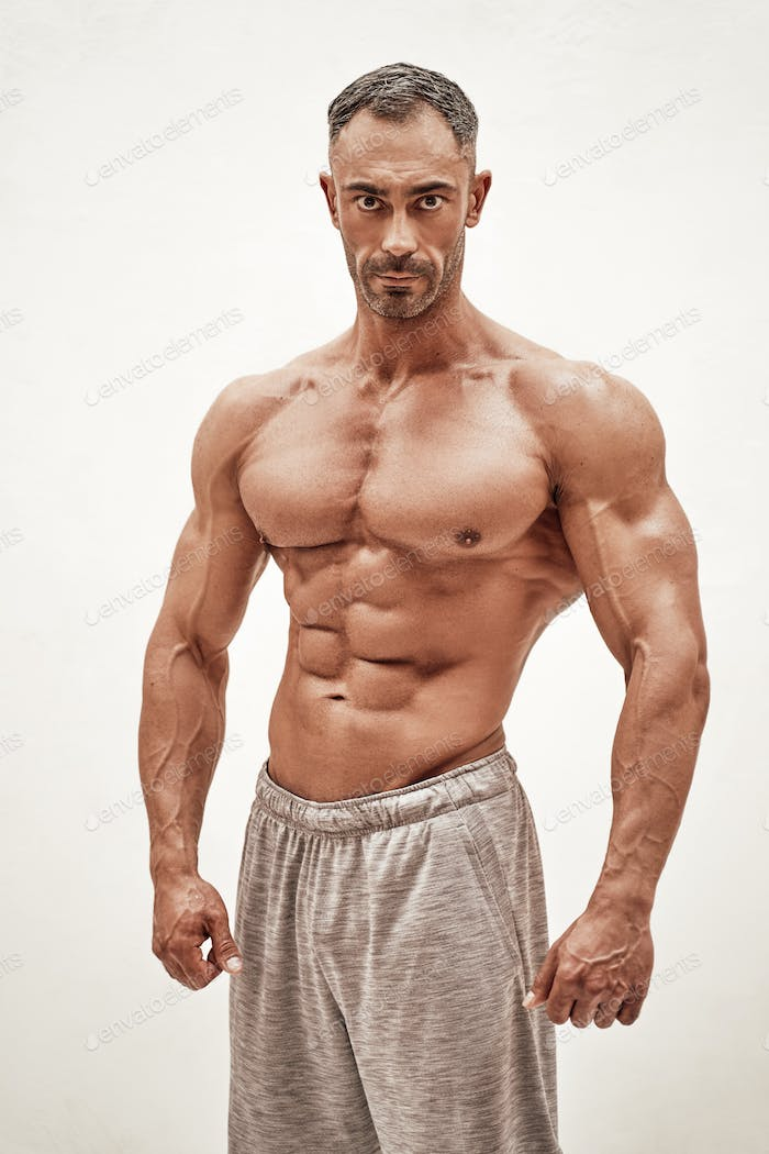 Shirtless sporty caucasian male isolated on a white concrete background