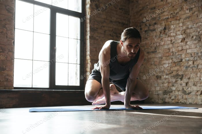 Attractive strong sportsman in gym make yoga sport exercises