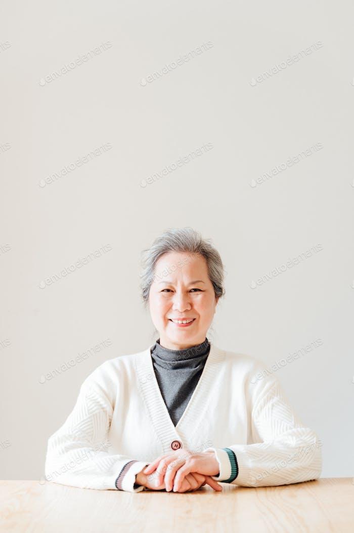 Porträt der Seniorin sitzt am Tisch